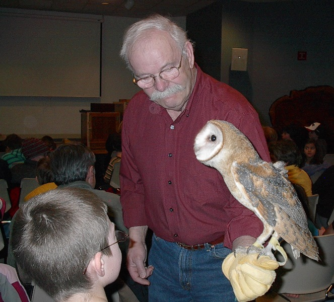 boy taking a close look at an owl during nature program